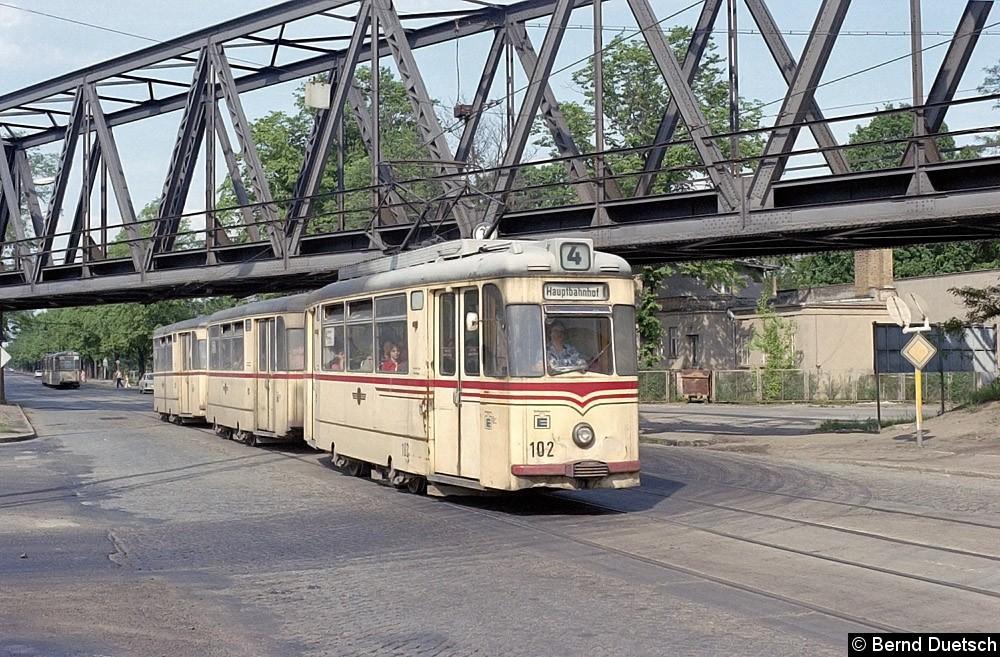Tw 102 fährt mit seinen zwei Beiwagen über die Leninallee (heute Zeppelinallee). Er wird gleich sein Ziel am Potsdamer Hauptbahnhof (heute Bf. Pirschheide) erreicht haben.